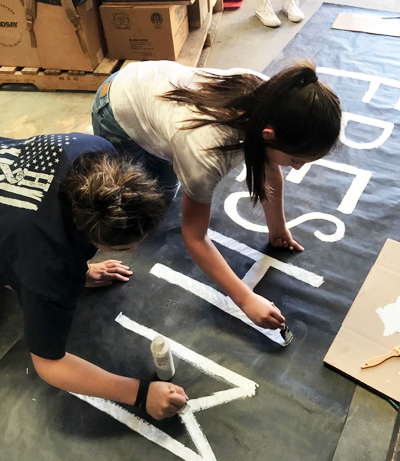 First float-- Freshmen Bretlei Dominguez and Cathryn Johnson work on the class of 2021's float after school on Sept. 20.