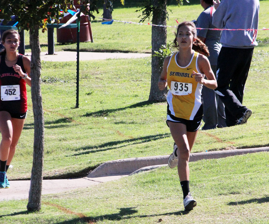 Looking ahead-- Freshman Hailey Davis looks at the course ahead during the district race at Mae Simmons Park on Oct. 12. As the district champion, Davis ran the same Lubbock course on Oct. 23 to qualify for state.