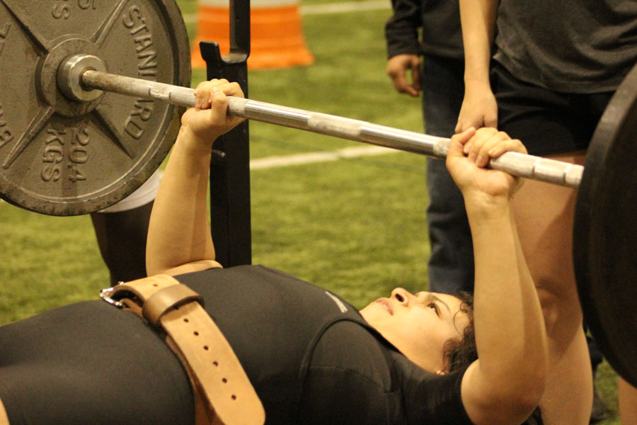 State bound--Sophomore Siria Martinez bench presses during the home meet on Feb. 1. Martinez lifted a combined 785 pounds in the 181-pound category to qualify for state on March 3.