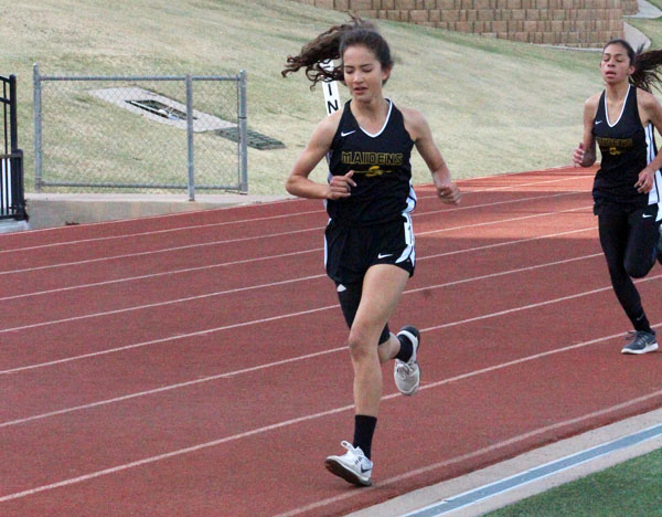 Friendly competition--Freshman Azalia Contreras catches freshman Hailey Davis in the 800-meter run at the district meet on April 7. Contreras would qualify for area in second place, with Davis qualifying in third position.
