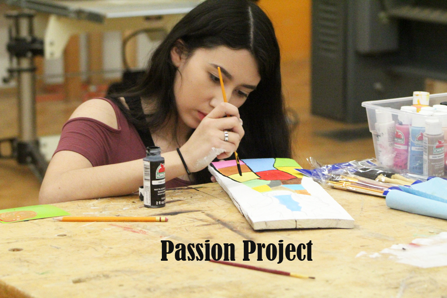Painting passion--Then junior Alé Morales Mendoza paints on a plank during one of her Passion Project classes on Nov. 11, 2017.