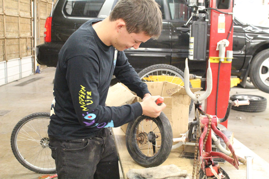 Yule retool-- Senior Herman Pipkin works on a tire for a bicycle in fifth period auto tech class. The bicycle was one of approximately 43 to be delivered to underprivileged children with the Give a Child a Smile service project for SkillsUSA.
