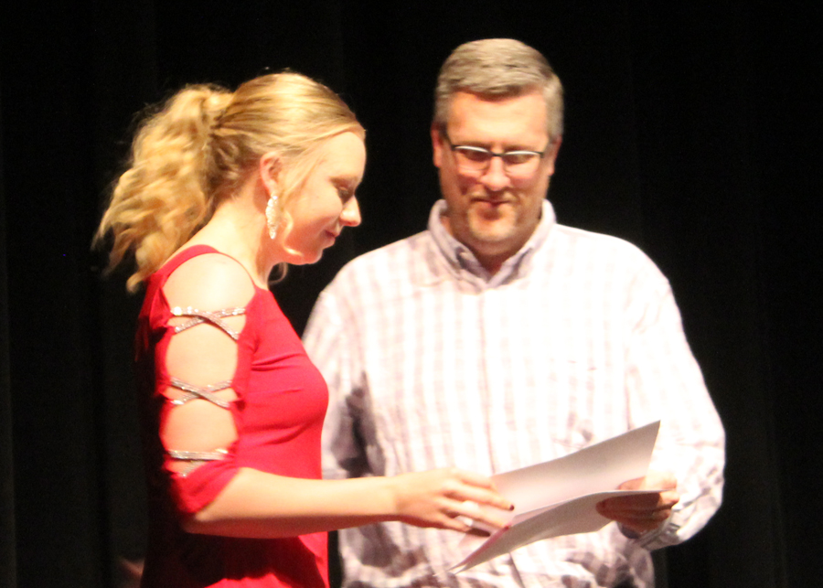 Cashing in-- Senior Brittney Weeks receives an athletic booster club scholarship from booster member Trey Duncan at the athletic awards presentation on 5-14. Weeks was one of nine seniors to receive scholarships at the event.