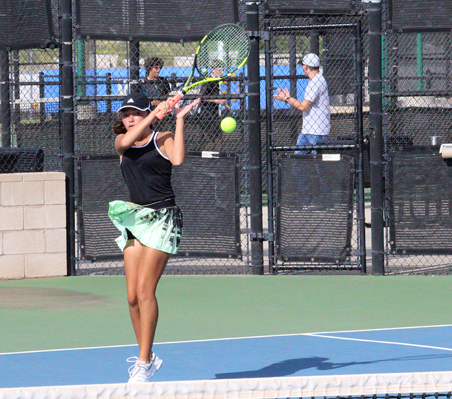 ADDING UP WINS-- Firing back a volley, sophomore Alyssa Gonzales and partner senior Jasmin Klassen take out the Andrews team of Aimee Mora and Mia Martinez during district play on Oct. 1. The 6-2, 6-3 win was one of 10 wins that day to clench the historic team tennis win.