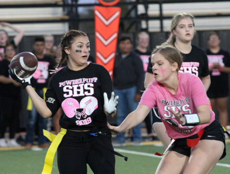 DEFENSIVE MOVE-- Senior Katy Beth Lashaway makes a grab for the flag of junior Andrea Neufeld during the powder puff match up on Oct. 17. The event was sponsored by the National Honor Society to fund chemotherapy care packages for cancer patients.