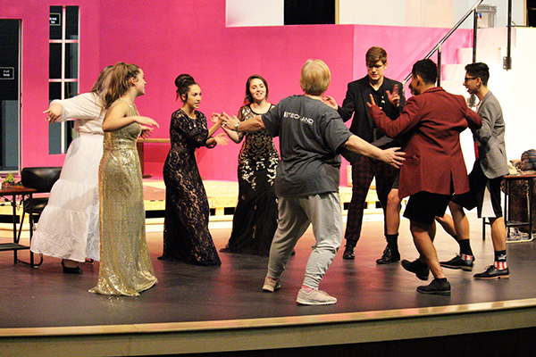 DRAMATIC WARM UP-- Theater teacher Vonya Eudy warms up the cast of 'Rumors' before practice on Sept. 30. The play will present three performances in the PAC.