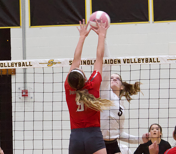 TIED UP-- Sophomore middle blocker Zoee Nolen challenges Denver City at the net during Oct. 22 non-district play. Nolan replaced senior middle blocker Rita Klassen who was ill.