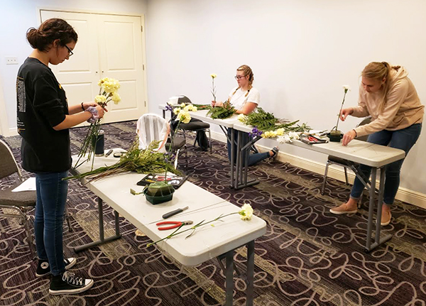 Getting certified-- Junior Kylie Lopez, junior Penelopi Neudorf and senior Elisabeth Hiebert Wiebe work on the level one floral certification hands-on test in October.