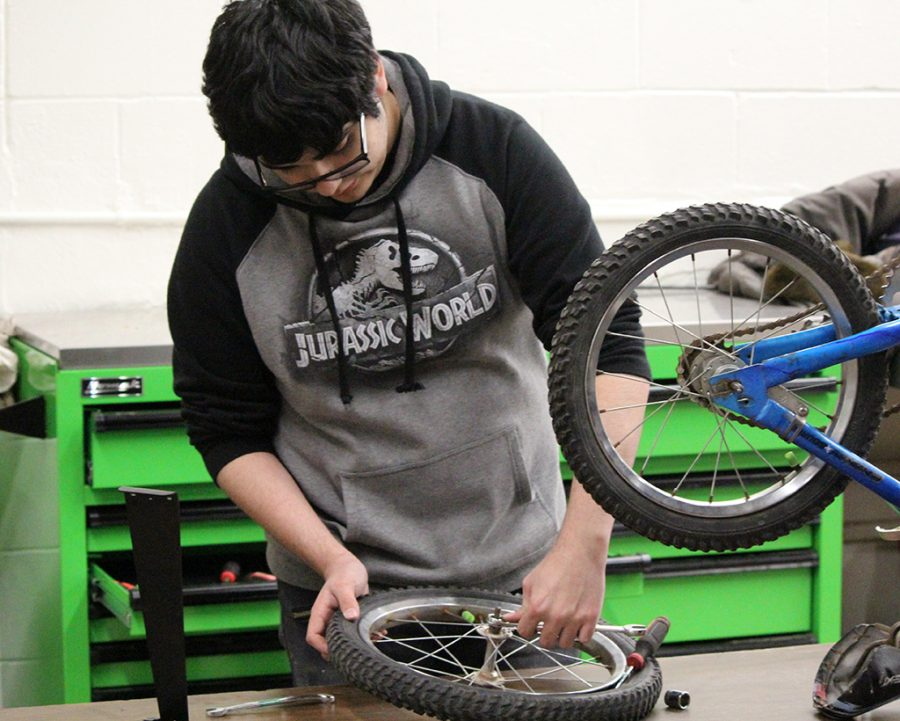 Refurbishing  for gifts-- Auto tech sophomore Izack Garcia works on a bicycle wheel during fourth period auto tech class in November. The auto tech class built or refurbished 57 new and used bikes for the Give a Child a Smile project.