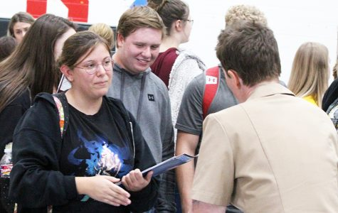"Looking for a future-- With an armful of pamphlets and fliers, junior Montana Morales talks to a military representative during College Day in the upper gym on Oct. 10. Morales said she has decided to go to junior college to get her basics out of the way. ""Then I want to go to a university to study biology to become a conservationist to try and save anything,"" Morales said."