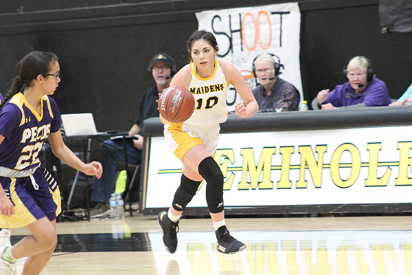 Popular sport-- With three radio stations broadcasting in the background, junior guard Bretlei Dominguez brings the ball down on the break during the Maidens' 82-14 win over Pecos on Feb. 7.