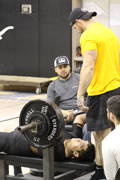 Region qualifer-- Indian Coach Call Barnard gets ready to spot junior Irvin Delgado in the bench press during the Big Spring meet on Jan. 11. Delgado qualified for regionals with a total wight of 1,240 pounds which put him in ninth position in the region.