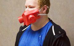 Mask maker Senior Justin Knelsen wears a mask he made with his 3D printer during quarantine. Knelsen now sells his homemade masks.