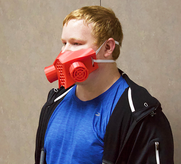 Mask maker senior Justin Knelsen wears a mask he made with his 3D printer during quarantine. Knelsen now sells his homemade masks.