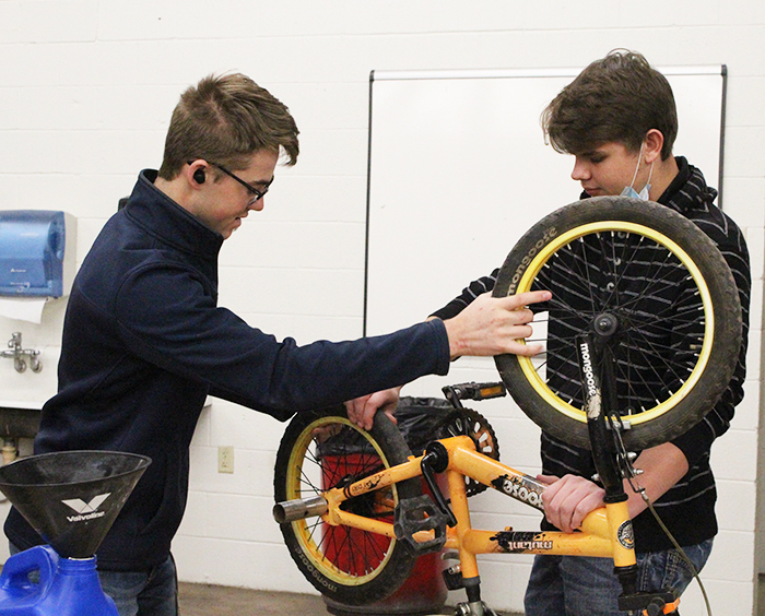 "Revamping a donation-- SkillsUSA junior David Koethler and senior Benny Hildebrand work on a bicycle during fourth period auto tech class. The group's ""Give a Child a Smile"" project took donations of bicycles and money to provide new and refurbished bikes to local children."