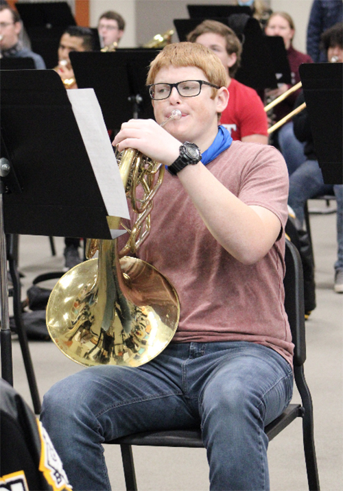 Songs of the season-- Band freshman Diedrich Friesen Wiebe plays French horn during the group's virtual performance on Dec. 16 during first period.
