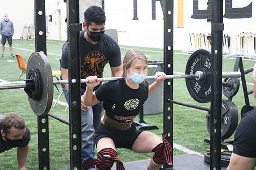 Taking the weight-- Junior Arielle Fehr squats 205 pounds at the home meet on Jan. 28. Fehr lifted a total of 505 pounds over the three events to take first place in the 123-pound division.