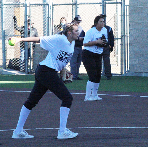 Back in the swing-- Senior pitcher Simone Roberson winds up for the throw while junior first baseman Natalie Deleon waits to field during the Feb. 9 scrimmage with Idalou. The Maidens will begin regular season play on Feb. 16 in Lamesa.