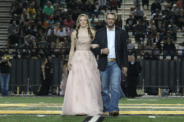 Freshman attendant-- Freshman Tatum Medlin is escorted across the field by her father Bobby during coronation on Sept. 18.