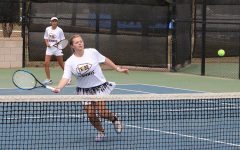Net ball--Senior Lauren Smith goes for the return as she and partner senior Marcela Guevara compete in district on the home courts on April 16. The pair would defeat Andrews for the championship in women's doubles.